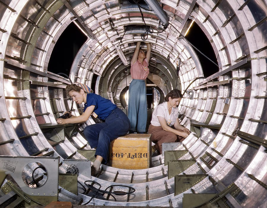 October 1942. Workers installing fixtures and assemblies in the tail section of a B-17F bomber at the Douglas Aircraft Company plant in Long Beach, California. 4x5 Kodachrome transparency by Alfred Palmer.