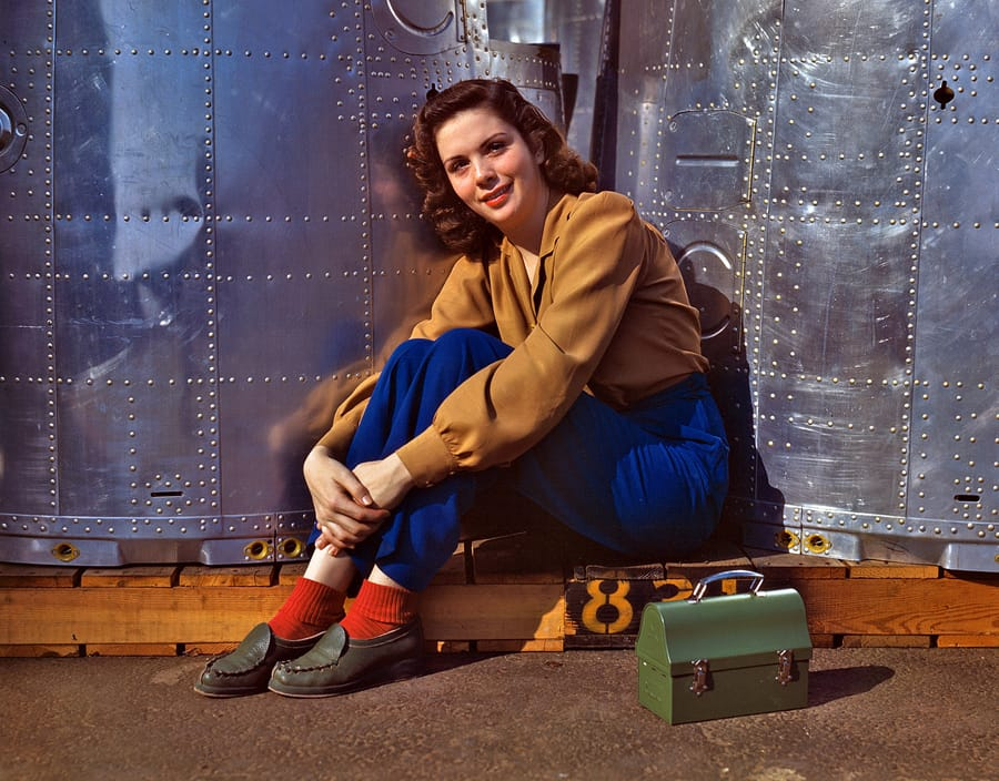 "October 1942. ""Noontime rest for an assembly worker at the Long Beach, Calif., plant of Douglas Aircraft Company. Nacelle parts for a heavy bomber form the background."" 4x5 Kodachrome transparency by Alfred Palmer."