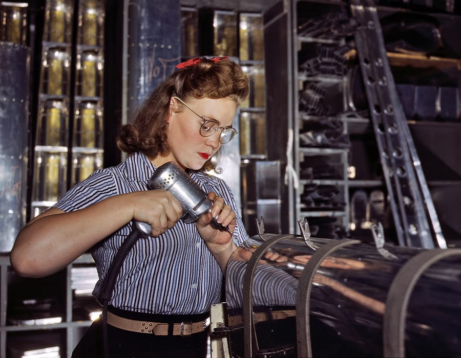 October 1942. Inglewood, California. North American Aviation drill operator in the control surface department assembling horizontal stabilizer section of an airplane. 4x5 Kodachrome transparency by Alfred Palmer.
