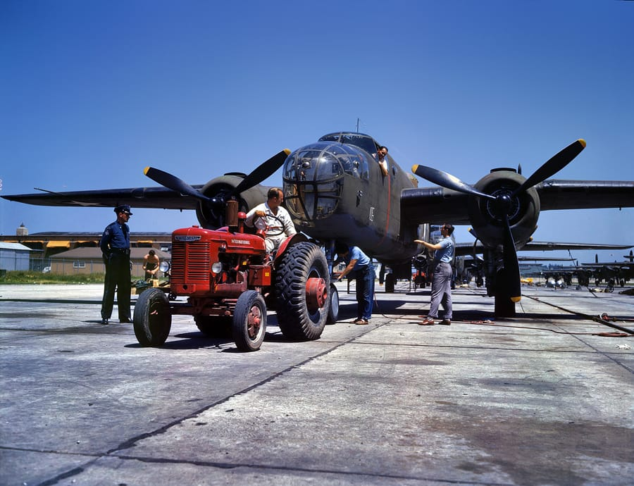 "October 1942. Kansas City, Kansas. ""B-25 bomber plane at North American Aviation being hauled along an outdoor assembly line."" 4x5 Kodachrome transparency by Alfred Palmer for the Office of War Information."