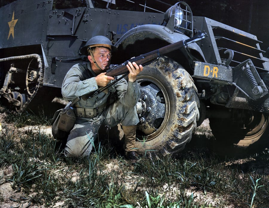 "June 1942. Fort Knox, Kentucky. ""Infantryman with halftrack. A young soldier sights his Garand rifle like an old-timer. He likes the piece for its fine firing qualities and its rugged, dependable mechanism."" 4x5 Kodachrome transparency by Alfred Palmer for the Office of War Information."