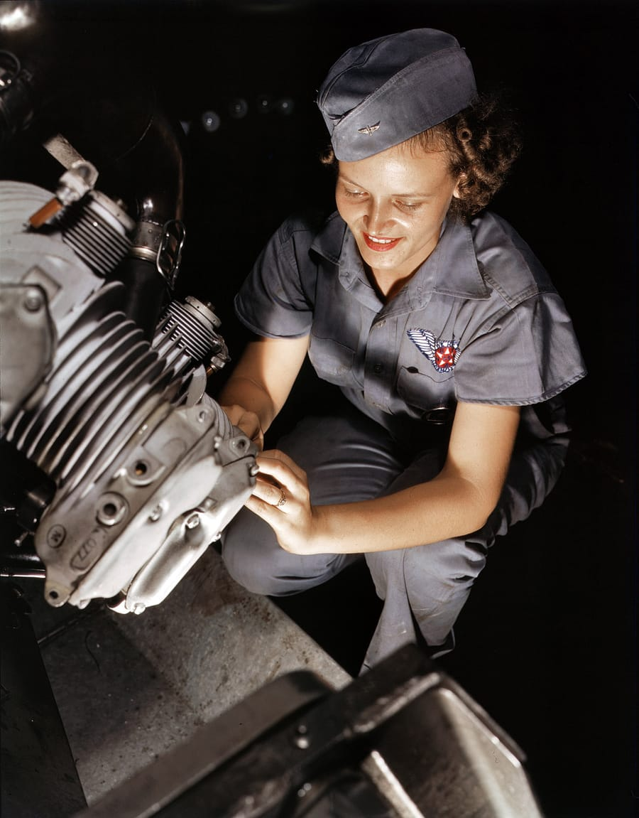 August 1942. Mechanic Mary Josephine Farley works on a Wright Whirlwind motor in the Corpus Christi, Texas, Naval Air Base assembly and repairs shop. 4x5 Kodachrome transparency by Howard R. Hollem.