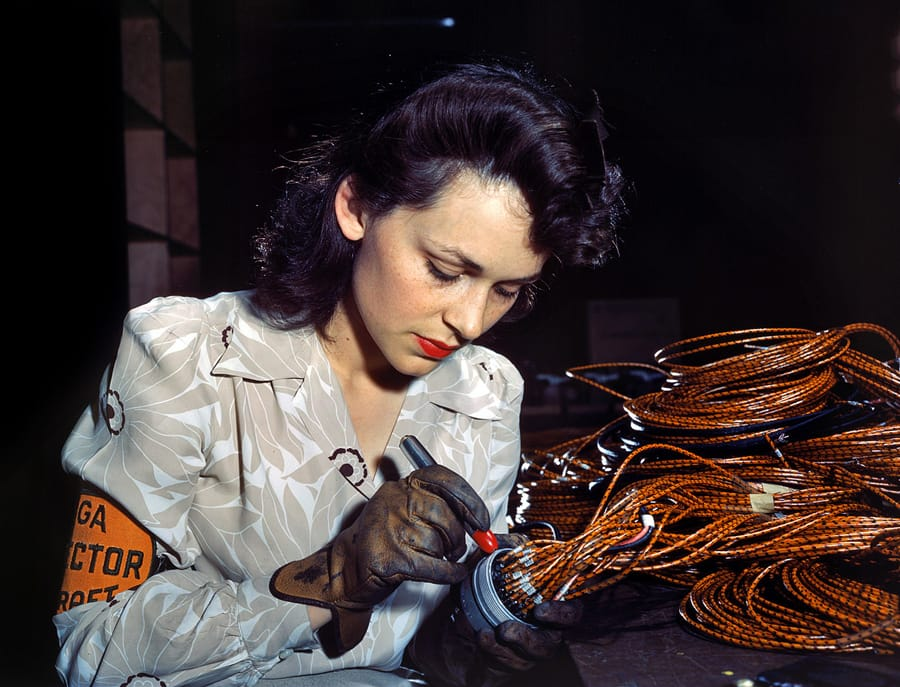 "June 1942. Lockheed Vega aircraft plant at Burbank, California. ""Hollywood missed a good bet when they overlooked this attractive aircraft worker, who is shown checking electrical sub-assemblies."" 4x5 Kodachrome transparency by David Bransby for the Office of War Information."